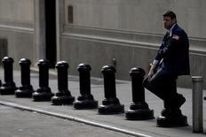 Трейдер отдыхает рядом с Нью-Йоркской фондовой биржей. Акции Уолл-стрит снизились во вторник, а основные индексы показали худший день почти за месяц, так как статистика и более слабые, чем ожидалось, продажи автомобилей спровоцировали опасения по поводу роста экономики.  REUTERS/Brendan McDermid