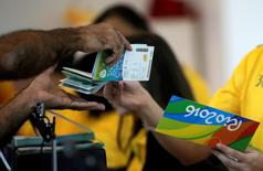 A salesman hands tickets to a sports fan after he bought them at the 2016 Rio Olympics ticket office in Rio de Janeiro Brazil, June 20, 2016. REUTERS/Ricardo Moraes/File Photo