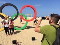 Reinaldo Maia tira foto de turistas que pagaram para posar com a tocha olímpica na praia de Copacabana. 04/08/2016 REUTERS/Pedro Fonseca
