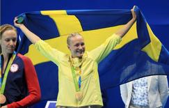 2016 Rio Olympics - Swimming - Victory Ceremony - Women's 100m Butterfly Victory Ceremony - Olympic Aquatics Stadium - Rio de Janeiro, Brazil - 07/08/2016. Sarah Sjostrom (SWE) of Sweden holds her national flag after winning the gold.    REUTERS/Dominic Ebenbichler