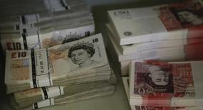 Пачки банкнот британского фунта в офисе компании GSA в Вене. 22 июля 2013 года. Средняя заработная плата руководителей компаний, входящих в британский индекс FTSE 100, выросла более чем на 10 процентов в 2015 году до 5,5 миллиона фунтов, согласно исследованию, которое, скорее всего, укрепит желание премьер-министра Терезы Мэй ограничить завышенный заработок. REUTERS/Leonhard Foeger