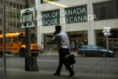 A man is reflected in a window while walking past the Bank of Canada office in Ottawa, Ontario, Canada, May 25, 2016. REUTERS/Chris Wattie - RTSFVZD