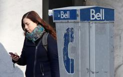 A woman uses a mobile device while walking past a Bell payphone in Ottawa February 19, 2014. REUTERS/Chris Wattie