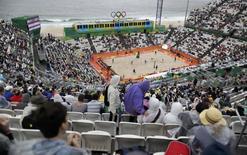 2016 Rio Olympics - Beach Volleyball - Men's Preliminary - Beach Volleyball Arena - Rio de Janeiro, Brazil - 10/08/2016. Fans watch beach volleyball on a rainy day.  REUTERS/Ricardo Moraes
