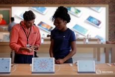 Сотрудник магазина Apple рассказывает о продукции компании в Бруклине 28 июля 2016 года. Объём розничных продаж в США неожиданно остался неизменным в июле, поскольку американцы уменьшили траты на одежду и другие товары, что указывает на замедление потребительских расходов и может снизить ожидания ускорения роста ВВП в третьем квартале.  REUTERS/Andrew Kelly