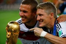 Germany's Lukas Podolski (L) and Bastian Schweinsteiger celebrate with the World Cup trophy after winning the 2014 World Cup final against Argentina at the Maracana stadium in Rio de Janeiro July 13, 2014. REUTERS/Kai Pfaffenbach
