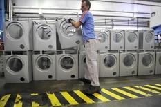 A worker arranges washing machines at a factory of Slovenia's largest household appliances maker Gorenje in Velenje May 11, 2010.  REUTERS/Srdjan Zivulovic
