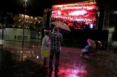 People stand in the rain while watching the 2016 Rio Olympics closing ceremony on a large screen in Rio de Janeiro August 21, 2016.  REUTERS/Pilar Olivares