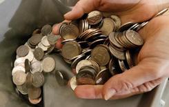 Кассир пересчитывает пятирублевые монеты в Красноярске. Рубль подешевел в начале торгов среды, реагируя на снижение нефти после данных о неожиданном росте её запасов в США, при этом сдерживать ослабление российской валюты могут оставшиеся потоки на продажу экспортной выручки под завтрашнюю уплату НДПИ, а также налога на прибыль 29 августа. REUTERS/Ilya Naymushin/File Photo