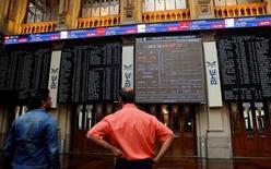 El Ibex-35 de la bolsa española cerró con alza en la sesión del miércoles a pesar de que buena parte de los valores que componen el principal índice terminaron bajando. En la imagen de archivo, dos hombres miran pantallas electrónicas en la Bolsa de Madrid. REUTERS/Andrea Comas
