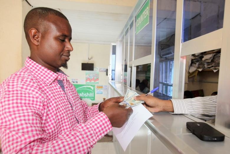 A customer receives U.S. notes from a teller at the Dahabshill money transfer office in capital Mogadishu February 16, 2015. REUTERS/Omar Faruk