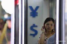 Женщина у пункта обмена валюты в Шанхае 14 августа 2015 года. Доллар повысился до месячного максимума против японской иены в ходе торгов среды, поскольку инвесторы изменили свои ожидания относительно перспектив повышения ставок ФРС США. REUTERS/Aly Song
