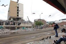 Oficiales de policía inspeccionan un edificio destruido por un terremoto que afectó a Ecuador, en Portoviejo. 6 de mayo de 2016 Ecuador prevé que su economía se contraerá un 1,7 por ciento en el 2016 debido a la caída de los precios del petróleo y los efectos de un devastador terremoto que azotó al país en abril, dijo el jueves el gerente del Banco Central, Diego Martínez. REUTERS/Guillermo Granja