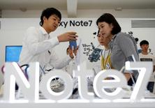 Продавец помогает покупателям в магазине Samsung в Сеуле 2 сентября 2016 года. Samsung Electronics Co Ltd заменит все смартфоны Galaxy Note 7 из-за возгорания батареи и приостановит продажи своего флагмана на десяти рынках, что может ударить по мобильному бизнесу компании, едва начавшему восстановление. REUTERS/Kim Hong-Ji
