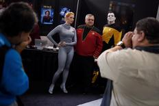 A man poses with people dressed as characters from various Star Trek television shows. REUTERS/Mark Kauzlarich