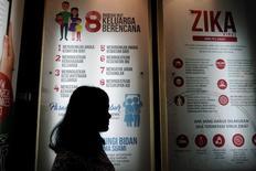 Женщина проходит мимо плаката с разъяснениями о вирусе Зика. Джакарта, 2 сентября 2016 года. Всемирная организация здравоохранения (ВОЗ) призвала мужчин и женщин, побывавших в регионах распространения вируса лихорадки Зика, на полгода воздержаться от секса или как минимум предохраняться, независимо от проявления симптомов. REUTERS/Iqro Rinaldi