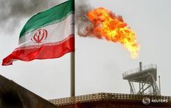 Флаг Ирана на нефтяной платформе в Персидском заливе 25 июля 2005 года. За последние три месяца уверенный рост добычи нефти в Иране сменился стагнацией, следует из свежих статистических данных, и это говорит о том, что Тегеран не может реализовать план роста производства, хотя и просит ОПЕК не включать его ни в какие соглашения об ограничении добычи. REUTERS/Raheb Homavandi/File Photo