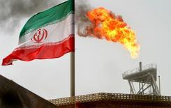 Una bandera de Irán cerca de una plataforma petrolera, en el Golfo. 25 de julio de 2005. El fuerte incremento de la producción de petróleo de Irán se ha estancado en los últimos tres meses, mostraron nuevos datos, lo que sugiere que Teherán podría estar teniendo dificultades para cumplir los planes de elevar su bombeo a nuevos máximos. REUTERS/Raheb Homavandi/File Photo