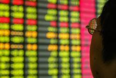 Un inversor chino mira un monitor que muestra información bursátil en una correduría en Shanghái. 12 de noviembre de 2003. Las acciones chinas cayeron el viernes luego de que el reporte de los datos de inflación de agosto no ofreció demasiados incentivo para que las autoridades relajen la política monetaria, lo que mantuvo a muchos inversores al margen. REUTERS/Claro Cortes IV/File Photo