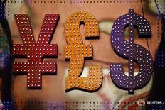 Символы валют доллар США (справа), фунт стерлингов (в центре) и иена в Гонконге 30 октября 2014 года. Доллар начал неделю в минусе, хотя потери и были ограничены из-за возобновившихся разговоров о вероятном повышении ставок ФРС США уже в сентябре. REUTERS/Damir Sagolj