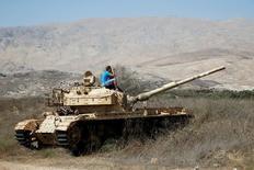 Человек сидит на старом танке, наблюдая за боями в Сирии со стороны Израиля на Голанских высотах 11 сентября 2016 года. Прекращение огня, о котором воюющие в Сирии силы договорились при посредничестве России и США, соблюдалось во вторник за редкими исключениями. REUTERS/Baz Ratner