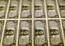 Billetes de un dólar en una mesa de luz en la Casa de Moneda de los Estados Unidos, en Washington, nov 14, 2014. El dólar caía el lunes desde un máximo de dos semanas, en momentos en que la fortaleza del petróleo era el tema principal en un mercado a la baja antes de las reuniones de política monetaria de los bancos centrales de Japón y Estados Unidos.  REUTERS/Gary Cameron/File Photo