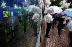 Un hombre mirando una pantalla que muestra el precio de las acciones, en Tokio, Japón. 18 de agosto de 2016. Las bolsas de Asia caían el martes, mientras los inversores esperan con nerviosismo el resultado de las reuniones de política monetaria de la Reserva Federal de Estados Unidos y del Banco de Japón, que concluirán el miércoles. REUTERS/Kim Kyung-Hoon