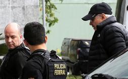 Гвидо Мантега в сопровождении полицейских прибыл в федеральную полицию. Бразильская полиция в четверг арестовала бывшего министра финансов страны Гидо Мантегу в рамках масштабного расследования дела о коррупции, сконцентрировавшегося на узком круге руководителей левой Партии трудящихся, возглавлявших страну 13 лет. REUTERS/Nacho Doce