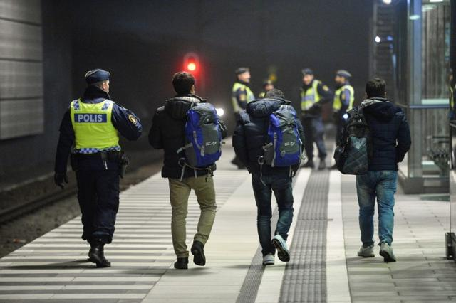 A police officer escorts migrants from a train at Hyllie station outside Malmo, Sweden, November 19, 2015. REUTERS/Johan Nilsson/TT NEWS AGENCY/File Photo