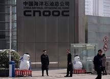 Security personnel stand next to snowmen at the entrance of China National Offshore Oil Corp (CNOOC) office tower in Beijing, March 20, 2013. REUTERS/Petar Kujundzic/File Photo