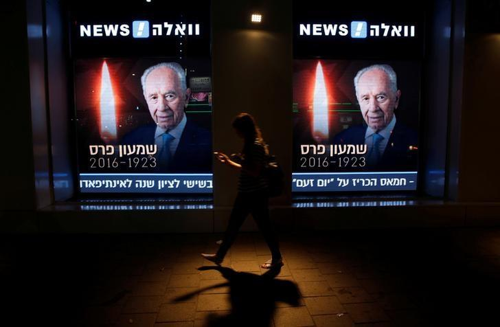 A woman walks by a wall outside a media building displaying photos of former Israeli President Shimon Peres in Tel Aviv, Israel September 28, 2016. REUTERS/ Baz Ratner