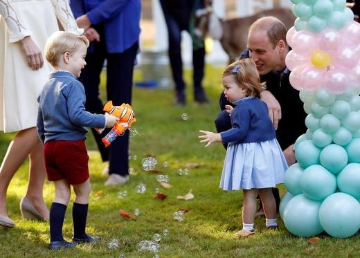 Britain's Prince William and Princess Charlotte look on as Prince George plays with a bubble gun at a children's party. Photo: Chris Wattie / Reuters