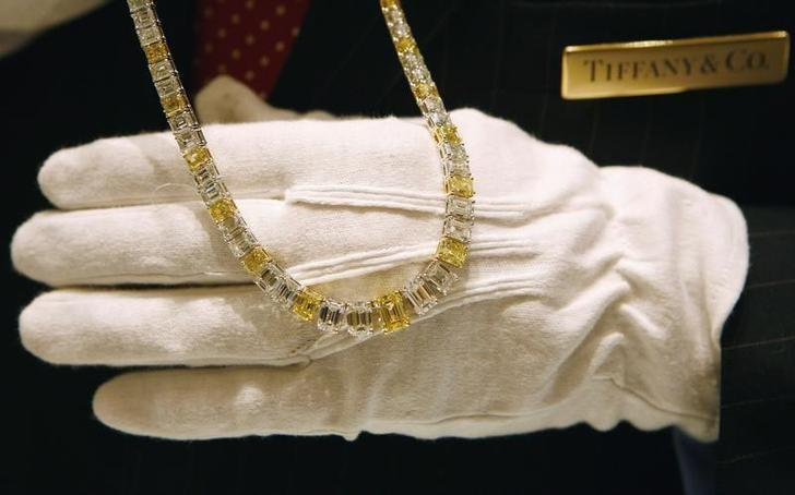 Tiffany and Co. salesman Peter Englehart displays a yellow emerald-cut diamond necklace selling for $1.2 million in their newest Tiffany and Co. store on Wall Street in New York City October 10, 2007.     REUTERS/Mike Segar/Files