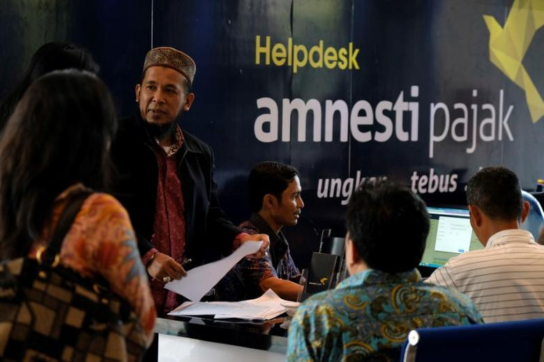 People wait at a help desk for tax amnesty at the country's tax headquarters in Jakarta, Indonesia September 30, 2016. REUTERS/Beawiharta