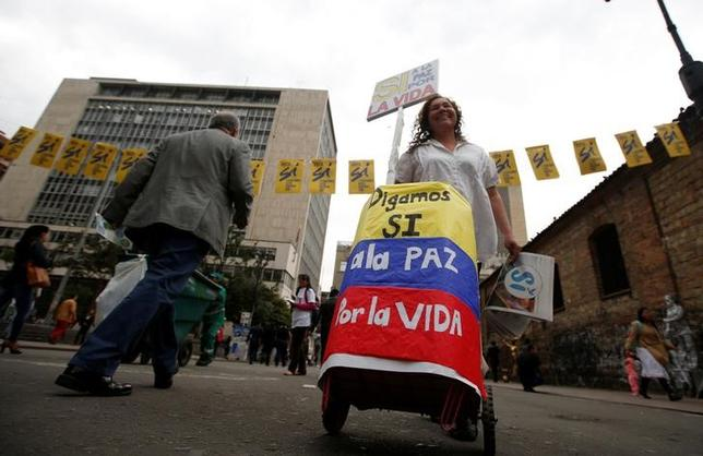 A street vendor walks under a banner supporting Colombian plebiscite in downtown in Bogota, Colombia, September 29, 2016. REUTERS/John Vizcaino/Files