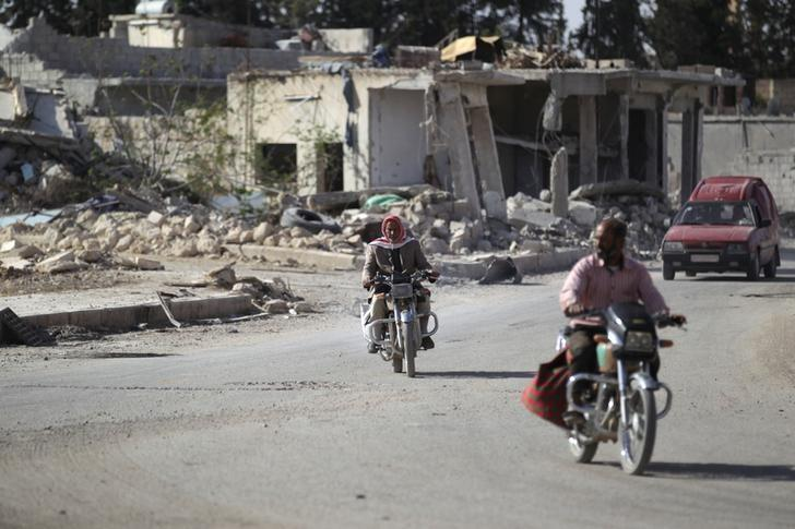 Men ride motorcycles past damaged buildings in al-Rai town, northern Aleppo countryside, Syria October 2, 2016. REUTERS/Khalil Ashawi
