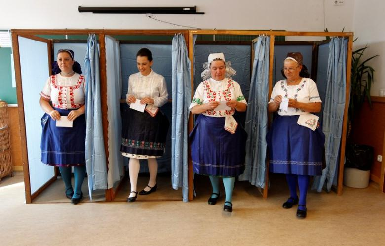Hungarian women wearing traditional costume leave a voting booth at a polling station during a referendum on EU migrant quotas in Veresegyhaz, Hungary, October 2, 2016. REUTERS/Bernadett Szabo