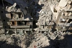 Люди ищут выживших в здании, пострадавшем от авиаудара, в Алеппо. 26 сентября 2016 года. Верховный комиссар ООН по правам человека Зейд Раад аль-Хусейн во вторник предостерег Россию от применения зажигательного оружия в осажденной восточной части сирийского Алеппо, сказав, что преступления, совершаемые одной из сторон конфликта, не оправдывают незаконных действий другой. REUTERS/Abdalrhman Ismail/File Photo