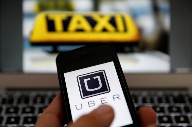 An illustration picture shows the logo of car-sharing service app Uber on a smartphone next to the picture of an official German taxi sign September 15, 2014.    REUTERS/Kai Pfaffenbach/Illustration/File Photo