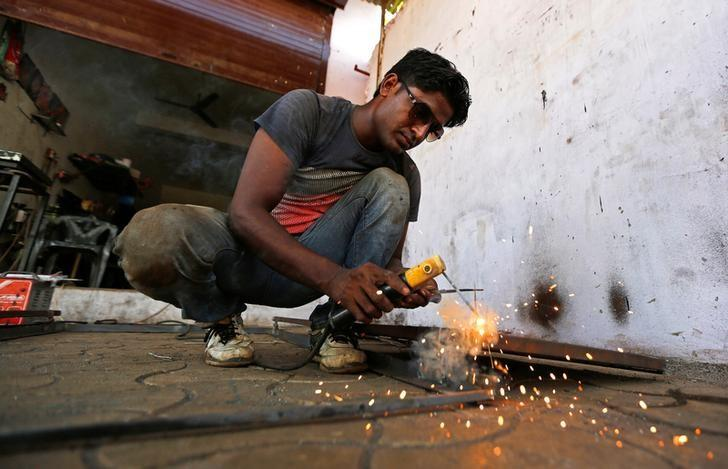 A worker welds a steel rod inside a door and window manufacturing unit on the outskirts of Ahmedabad, India, September, 12, 2016. REUTERS/Amit Dave