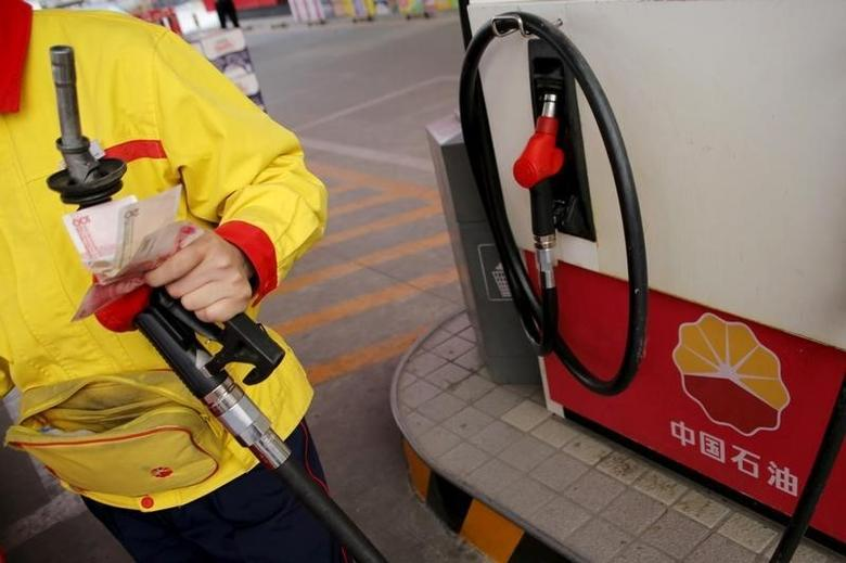 A gas station attendant pumps fuel into a customer's car at PetroChina's petrol station in Beijing, China, March 21, 2016.     REUTERS/Kim Kyung-Hoon/File Photo