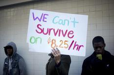 Демонстранты требуют повышения зарплат. Окленд, Калифорния, 5 декабря 2013 года. Неудовлетворительные темпы роста экономики США усугубили разрыв в уровне доходов между различными расовыми группами страны, заявил высокопоставленный чиновник ФРС в среду, предложив улучшить доступ американцев к более качественному образованию как способу повысить производительность труда и объемы производства. REUTERS/Noah Berger