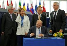 Президент Европарламента Мартин Шульц подписывает соглашение о борьбе с изменением климата. Глобальное соглашение о борьбе с изменением климата вступит в силу в ноябре, после преодоления в среду важного порога ратификации благодаря поддержке со стороны европейских государств.  REUTERS/Vincent Kessler