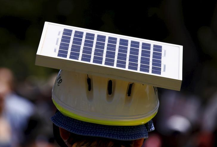 A cyclist wears a helmet with a solar panel attached along the main street of Adelaide, South Australia November 29, 2015.   REUTERS/David Gray/Files