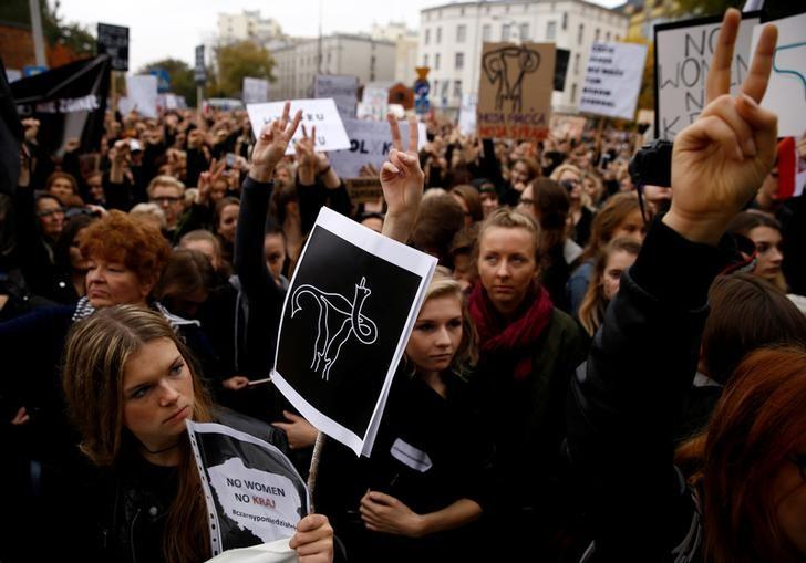 Women gesture as people gather in an abortion rights campaigners' demonstration to protest against plans for a total ban on abortion in front of the ruling party Law and Justice (PiS) headquarters in Warsaw, Poland October 3, 2016. REUTERS/Kacper Pempel/File photo