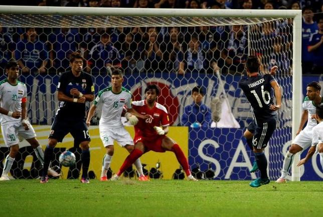 10月6日、サッカーの2018年W杯ロシア大会アジア最終予選B組の日本代表は、埼玉スタジアムでイラクに2─1と辛勝。写真は山口蛍(背番号16)が決勝点を決めた場面(2016年 ロイター/Issei Kato)