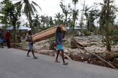 """Люди несут гроб после удара стихии по Men carry a coffin after Hurricane Matthew hit Кавайон, Гаити, 6 октября 2016 года. Ураган """"Мэттью"""", самый мощный в Карибском море за последние девять лет, унес как минимум 283 жизни на Гаити, сообщили в четверг спасатели. REUTERS/Andres Martinez Casares"""