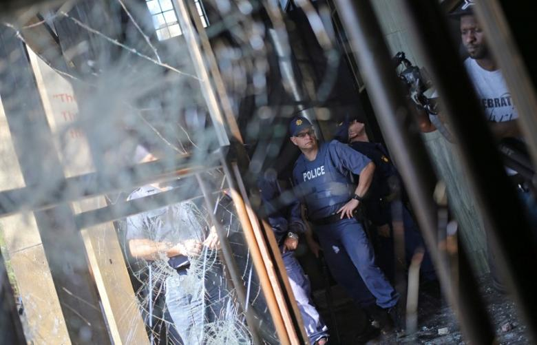 A police officer looks at a damaged window after students clashed with security at University of the Witwatersrand as countrywide protests demanding free tertiary education entered a third week, Johannesburg, South Africa, September 20, 2016. REUTERS/Siphiwe Sibeko