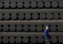 Un trabajador caminando junto a pilas de productos de acero en una planta en Tangshan, China. 3 de noviembre de 2015. La Unión Europea ha establecido aranceles provisionales a la importación de dos tipos de acero que llegan al bloque desde China para compensar lo que considera precios injustamente bajos, en un movimiento que probablemente enfade a Pekín. REUTERS/Kim Kyung-Hoon/File Photo