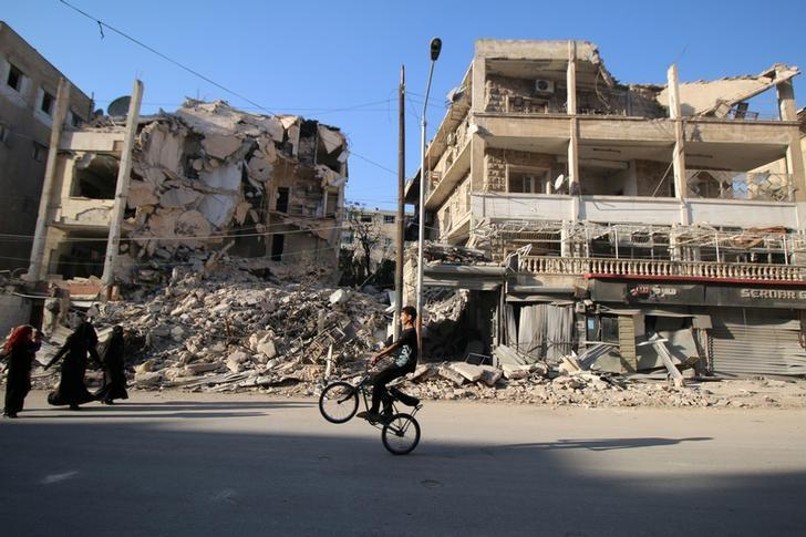 A boy plays with a bicycle past damaged buildings in the rebel held Seif al-Dawla neighbourhood of Aleppo, Syria October 6, 2016. REUTERS/Abdalrhman Ismail